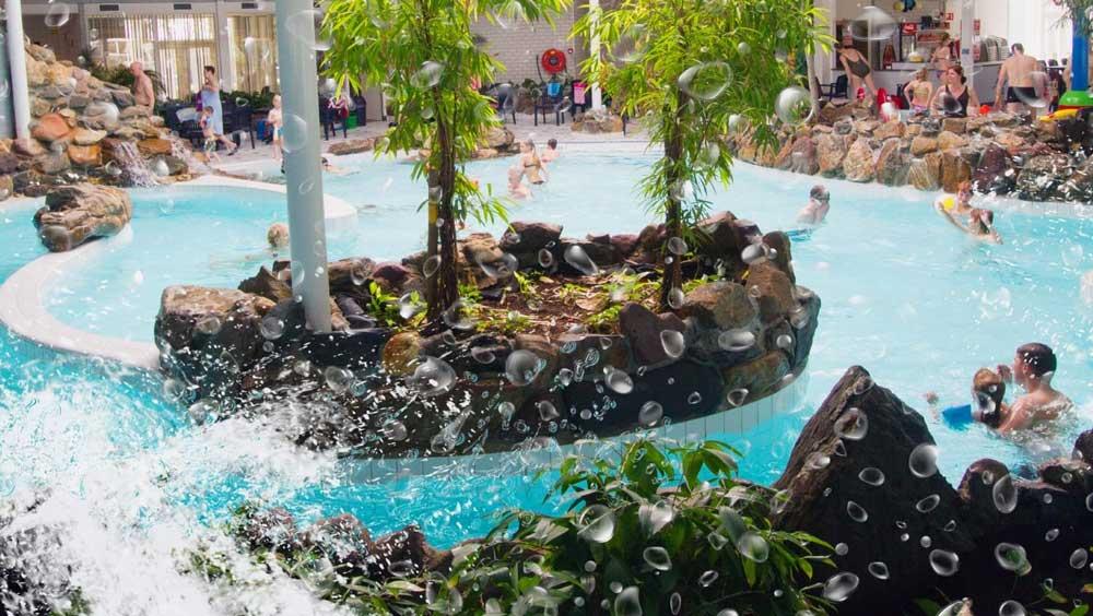 Subtropisch zwemparadijs binnen op dit vakantiepark en een golfslagbad en zwemvijver buiten